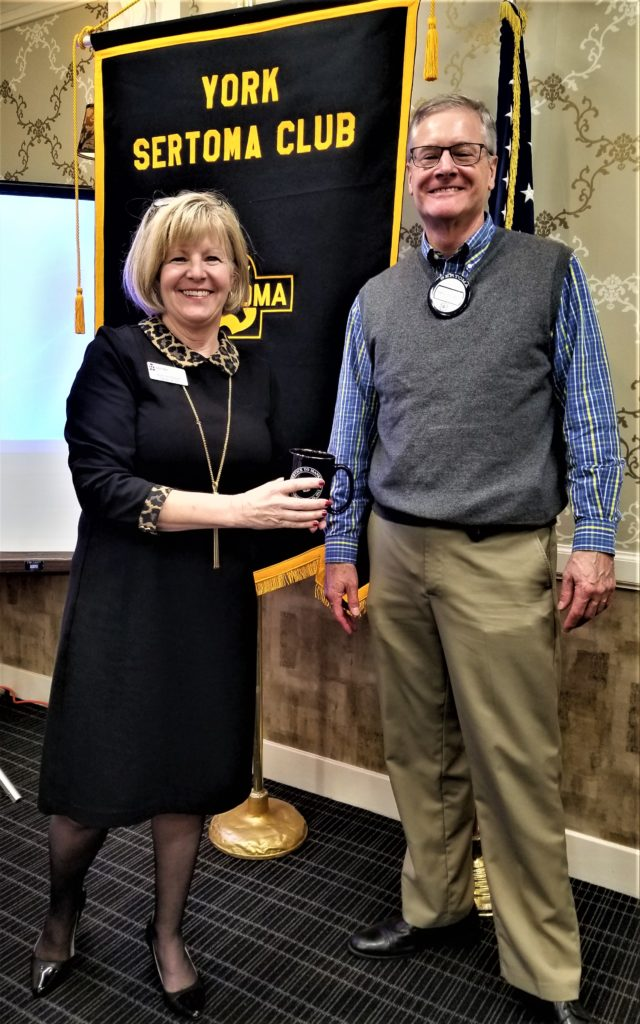 Joan Mummert (L) of the York County History Center receiving a coffee mug from York Sertoma President Jim Gross. On January 16, Joan presented information about the History Center and its consolidation into the former MetEd Steam Plant at Philadelphia Street and Pershing Avenue in York.